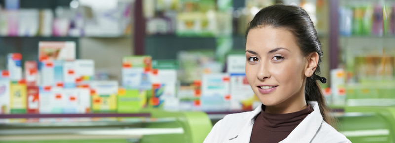 Pharmacist in front of counter displays.